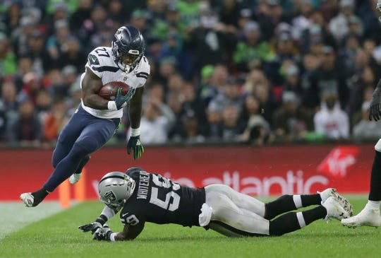 Seattle Seahawks running back Mike Davis (left) escapes the clutches of Oakland Raiders linebacker Tahir Whitehead (59).