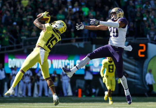 Oregon cornerback Deommodore Lenoir (15), intercepts a pass intended for Washington wide receiver Ty Jones (20), ending Washington's first drive and setting up an Oregon field goal.