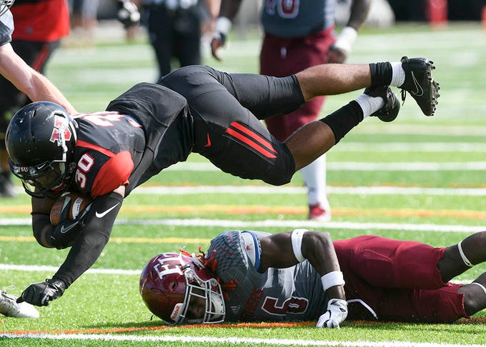 Seth McGill of Valdosta State dives over Florida Tech's John McClure and scores a touchdown during Saturday's game.