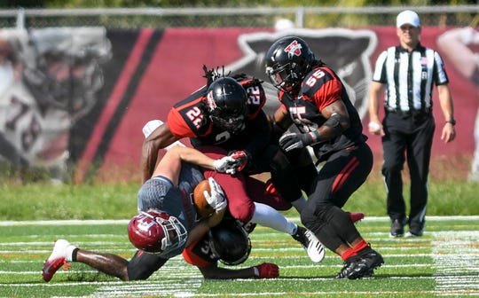 Kenny Hiteman of Florida Tech is corralled by Aaron Dawson (31) Donte Carpenter (55) and Isaiah Johnson (22) during Saturday's game.