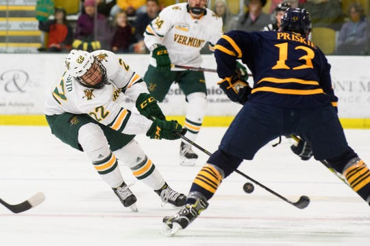 Vermont forward Alex Esposito (22) battles for the puck with Quinnipiac's Chase Priskie (13) during the men's hockey game between the Quinnipiac Bobcats and the Vermont Catamounts at Gutterson Field House on Saturday night October 13, 2018 in Burlington. (BRIAN JENKINS/for the FRESS PRESS)