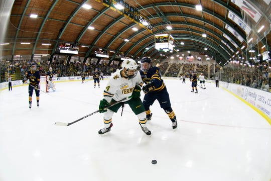 Quinnipiac's Zach Mesta (23) battles for the puck with Vermont defenseman Owen Grant (4) during the men's hockey game between the Quinnipiac Bobcats and the Vermont Catamounts at Gutterson Field House on Saturday night October 13, 2018 in Burlington. (BRIAN JENKINS/for the FRESS PRESS)