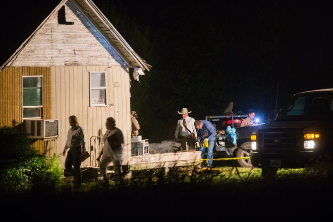 Law enforcement officials work a crime scene after a shooting left four dead in Taft on Saturday.