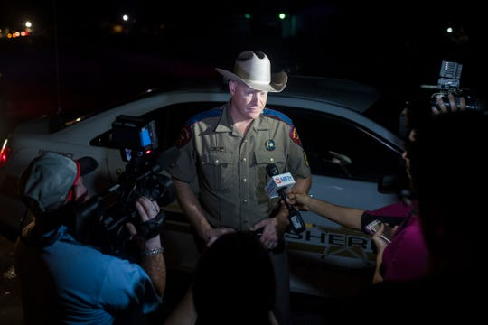 Department of Public Safety Trooper Nathan Brandley addresses the media outside a crime scene after a shooting left four dead in Taft on Saturday.
