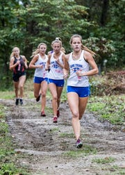 Zane Trace's Abbey Mohan leads a pack of girls in the woods of the Hopkins Farm in Huntington Township during the 2018 Scioto Valley Conference Cross Country Championships.  Mohan took first out of 49 runners with a total time of 20:15 and helped to clinch her team's first place finish with an average time of 22:23.60, while the Unioto girls' team took second place with an average time of 24:14.00.