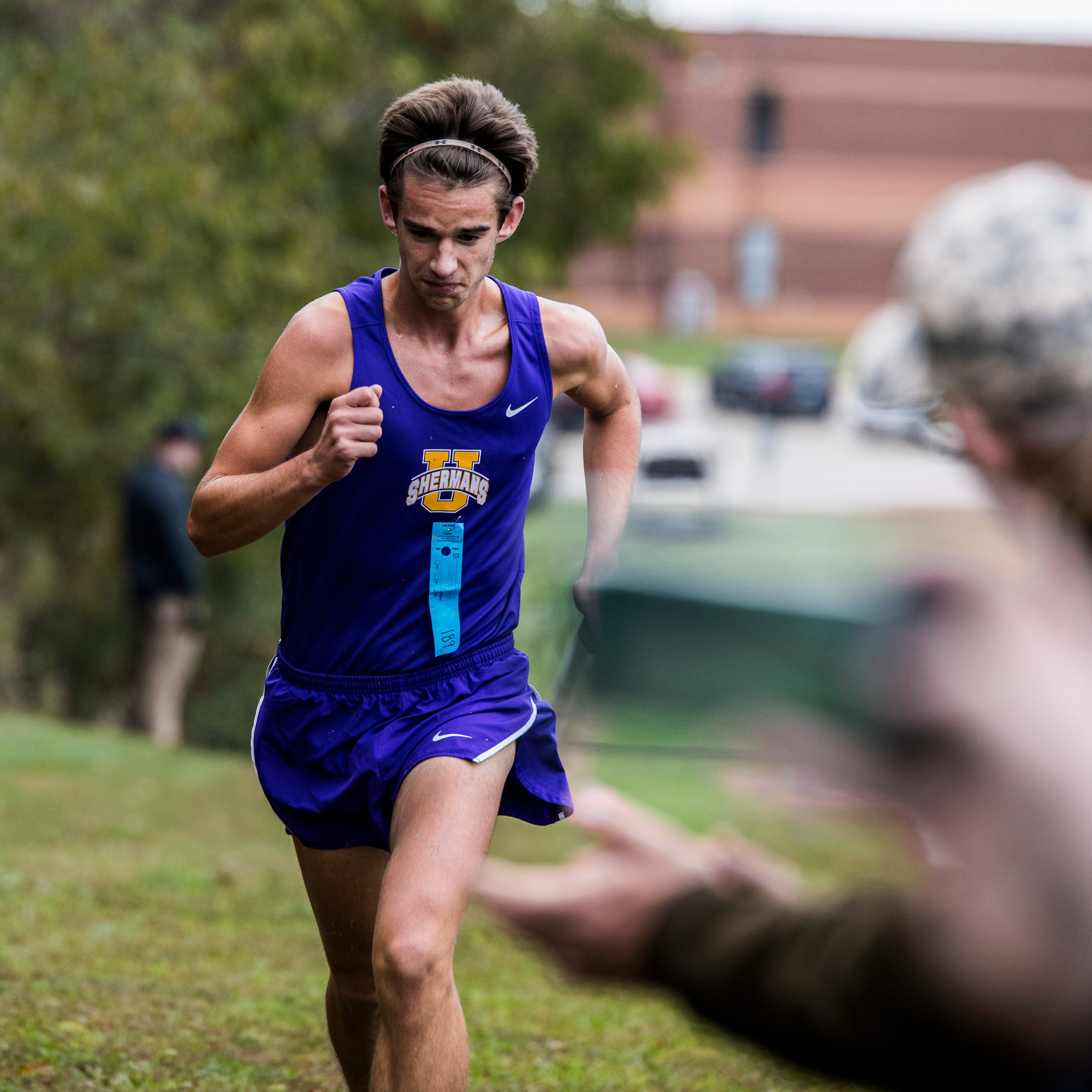 The crowd cheers and takes video as Unioto's Tucker Markko finishes first out of 65 runners with a total time of 16:30 at the 2018 Scioto Valley Conference Cross Country Championships held at the Hopkins Farm in Huntington Township. The Unioto boys team would finish first place with an average time of 16:58.20 and the Westfall boys team received second place with an average time of 18:34.60.