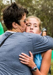 Allison Butler kisses her daughter Abby Butler, a senior from Adena, after completing her last Scioto Valley Conference Cross Country Championship in Huntington Township at the Hopkins Farm on Saturday, October 13, 2018.