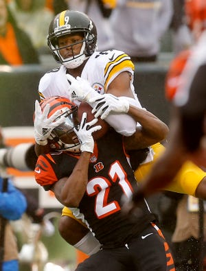 Cincinnati Bengals defensive back Darqueze Dennard (21) and Pittsburgh Steelers wide receiver JuJu Smith-Schuster (19) collide over the ball as JuJu Smith-Schuster is ruled to have made the catch near the goal line in the second quarter of the NFL Week 6 game between the Cincinnati Bengals and the Pittsburgh Steelers at Paul Brown Stadium in downtown Cincinnati on Sunday, Oct. 14, 2018. The game was tied 14-14 at half time.