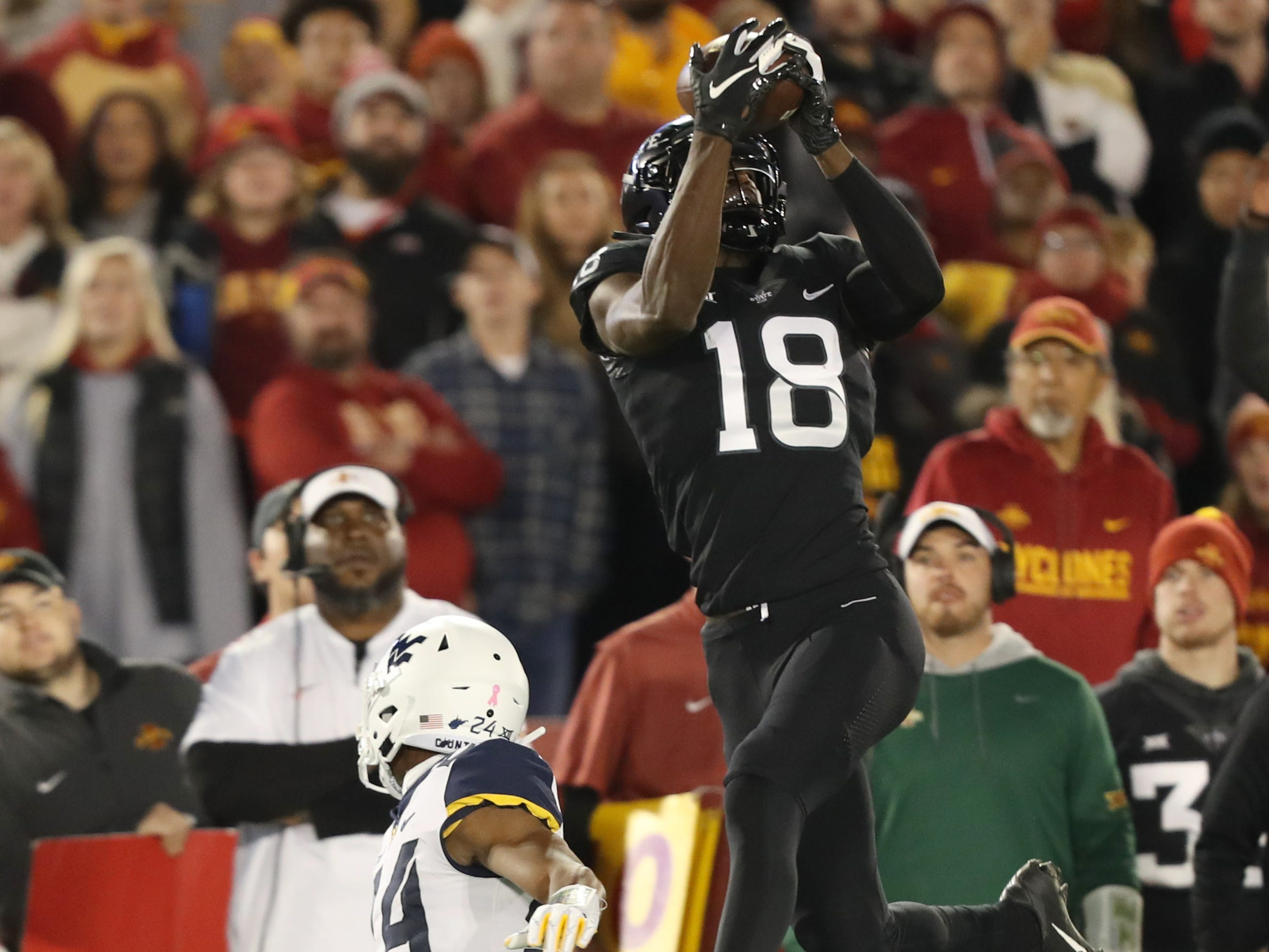 Iowa State Cyclones wide receiver Hakeem Butler (18) jumps over West Virginia Mountaineers safety Josh Norwood (4) for a catch at Jack Trice Stadium.