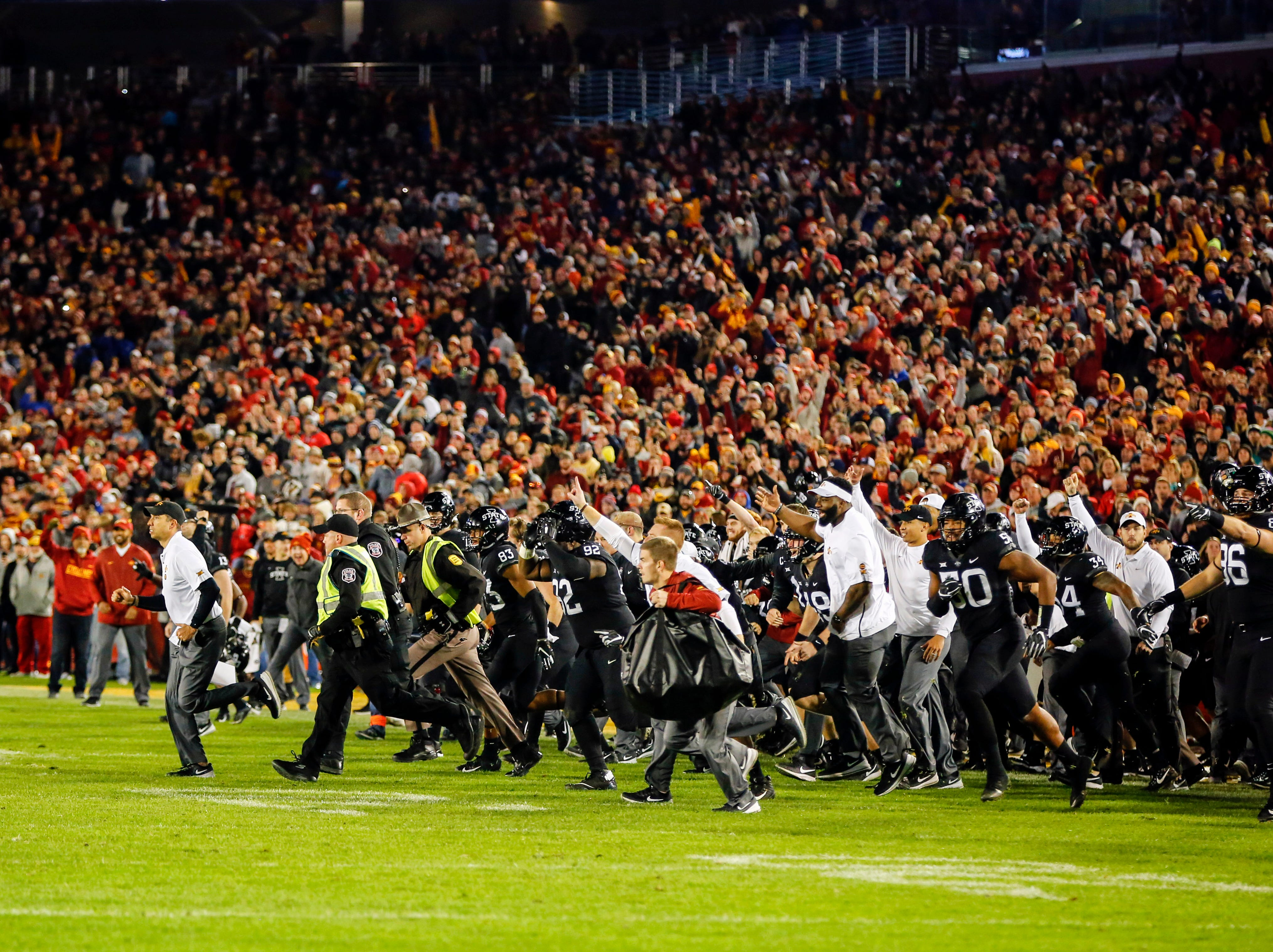 Iowa State players and staff take the field after defeating West Virginia at Jack Trice Stadium Saturday, Oct. 13, 2018.
