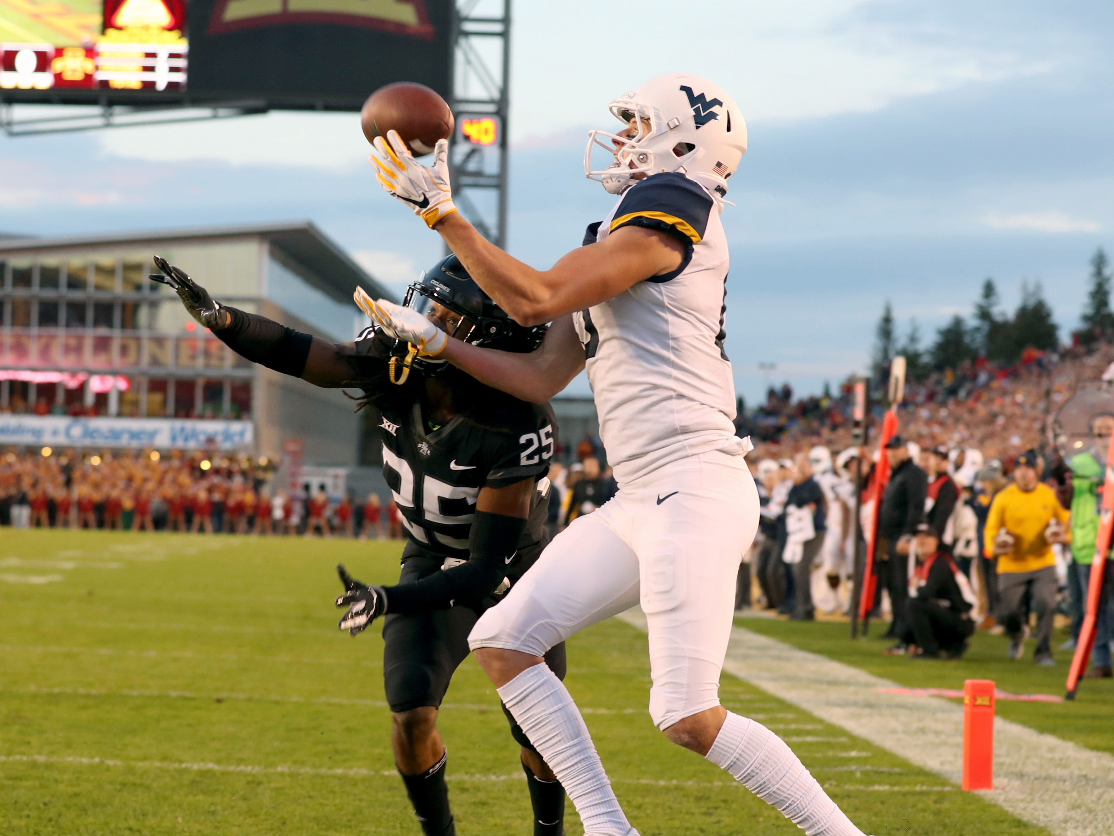 West Virginia Mountaineers wide receiver David Sills V (13) catches a touchdown pass against Iowa State Cyclones defensive back Datrone Young (25) at Jack Trice Stadium.