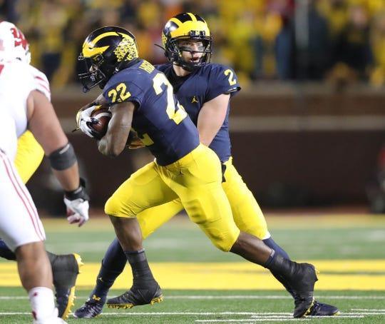 Michigan quarterback Shea Patterson hands off to Karan Higdon during the first half against Wisconsin, Saturday, Oct. 13, 2018 at Michigan Stadium in Ann Arbor.