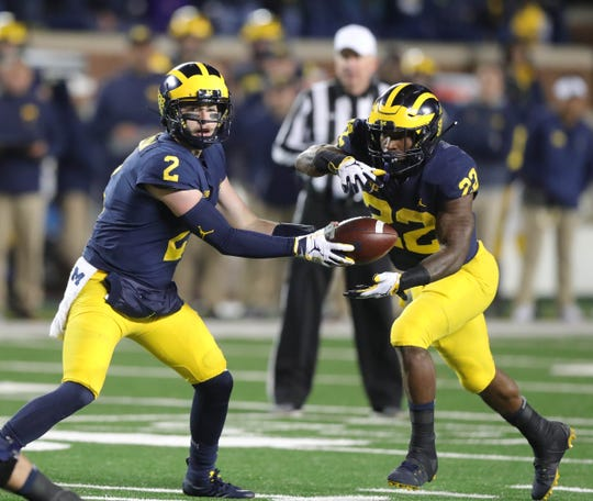 Michigan quarterback Shea Patterson hands off to Karan Higdon against Wisconsin, Saturday, Oct. 13, 2018 at Michigan Stadium in Ann Arbor.
