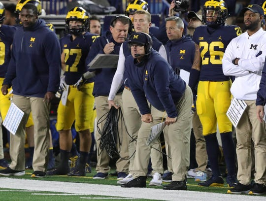 Michigan coach Jim Harbaugh (center) and offensive line coach Ed Warinner (left with the headset) watch the second half against Wisconsin on Saturday, Oct. 13, 2018 at Michigan Stadium in Ann Arbor.