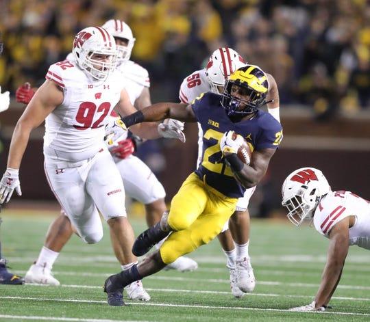 Michigan running back Karan Higdon runs by Wisconsin defenders during the second half Saturday, Oct. 13, 2018 at Michigan Stadium in Ann Arbor.