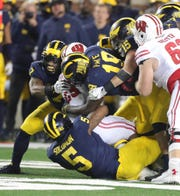 Michigan defenders tackle Wisconsin running back Jonathan Taylor during the second half Saturday, Oct. 13, 2018 at Michigan Stadium in Ann Arbor.