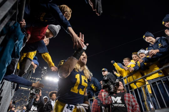 Michigan defensive lineman Chase Winovich high-fives the fans while walking off the field after the Wisconsin game.