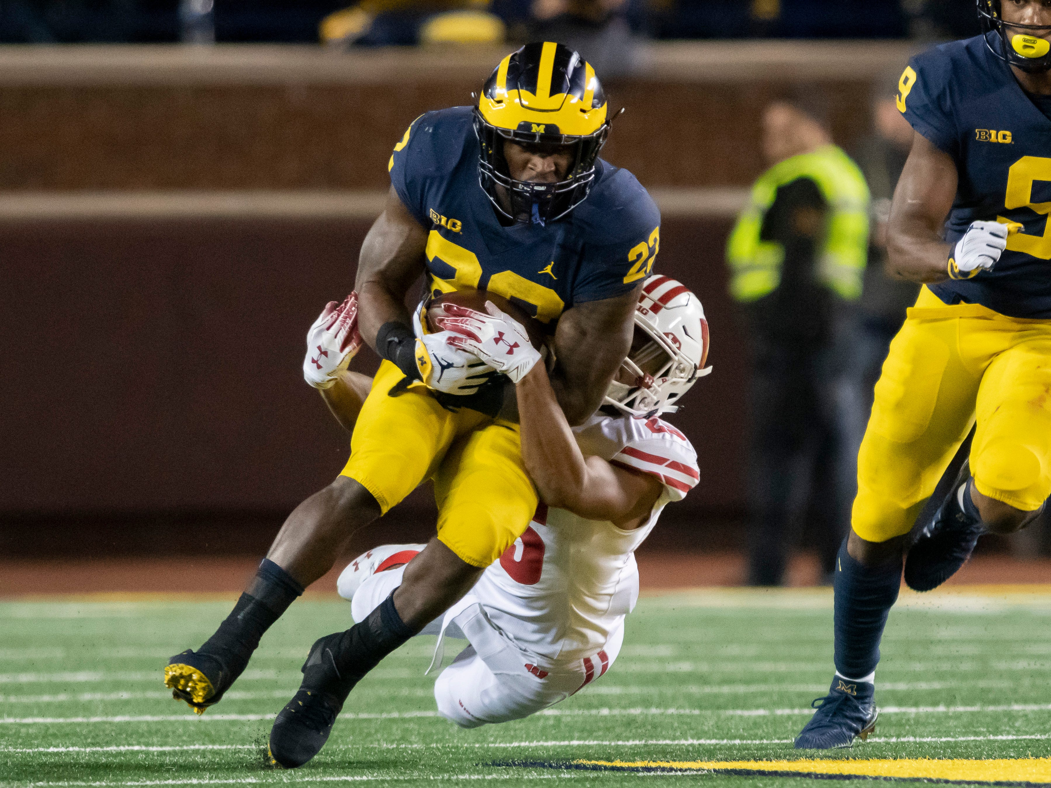 Michigan running back Karan Higdon runs the ball while being tackled by Wisconsin safety Eric Burrell in the third quarter.