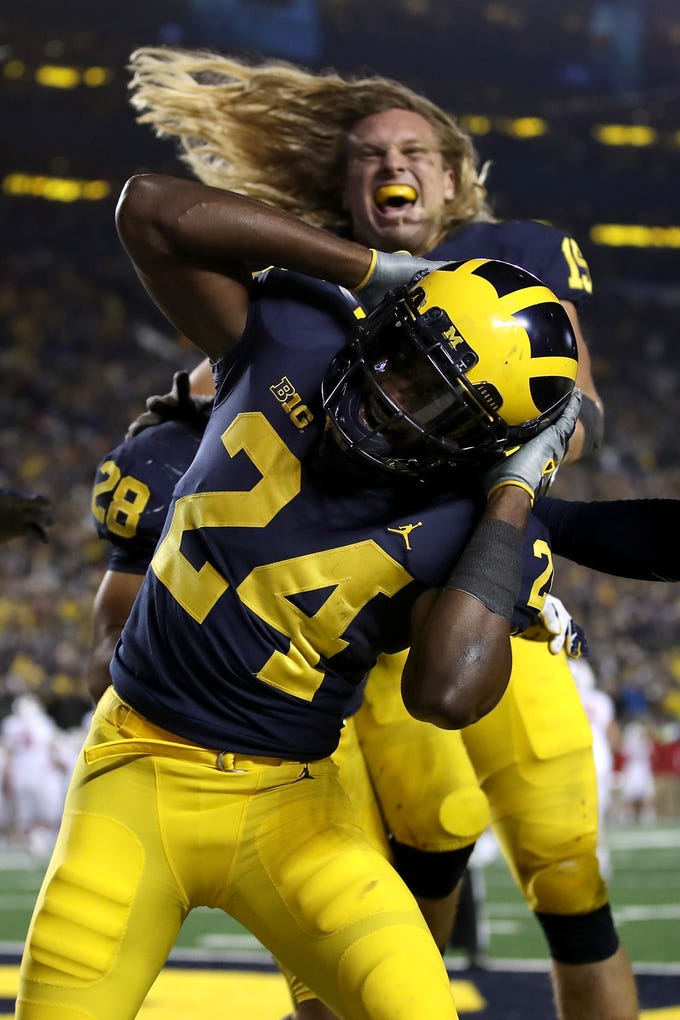"""Lavert Hill #(24) and Chase Winovich enjoyed the heck out of Saturday's victory over Wisconsin, which featured the presence of ESPN's """"College GameDay."""" That means one thing: Hilarious signs. Here are some of our favorites (at least, the clean ones)."""