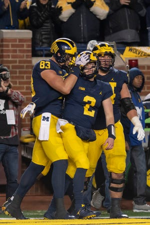 From left, Michigan tight end Zach Gentry, quarterback Shea Patterson, and offensive lineman Ben Bredeson celebrate after Patterson ran for a touchdown in the third quarter.
