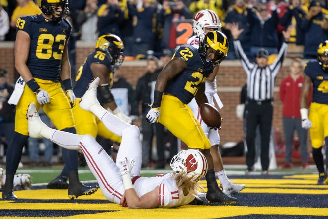 Michigan running back Karan Higdon shakes off Wisconsin linebacker Andrew Van Ginkel while running for a touchdown in the second quarter.