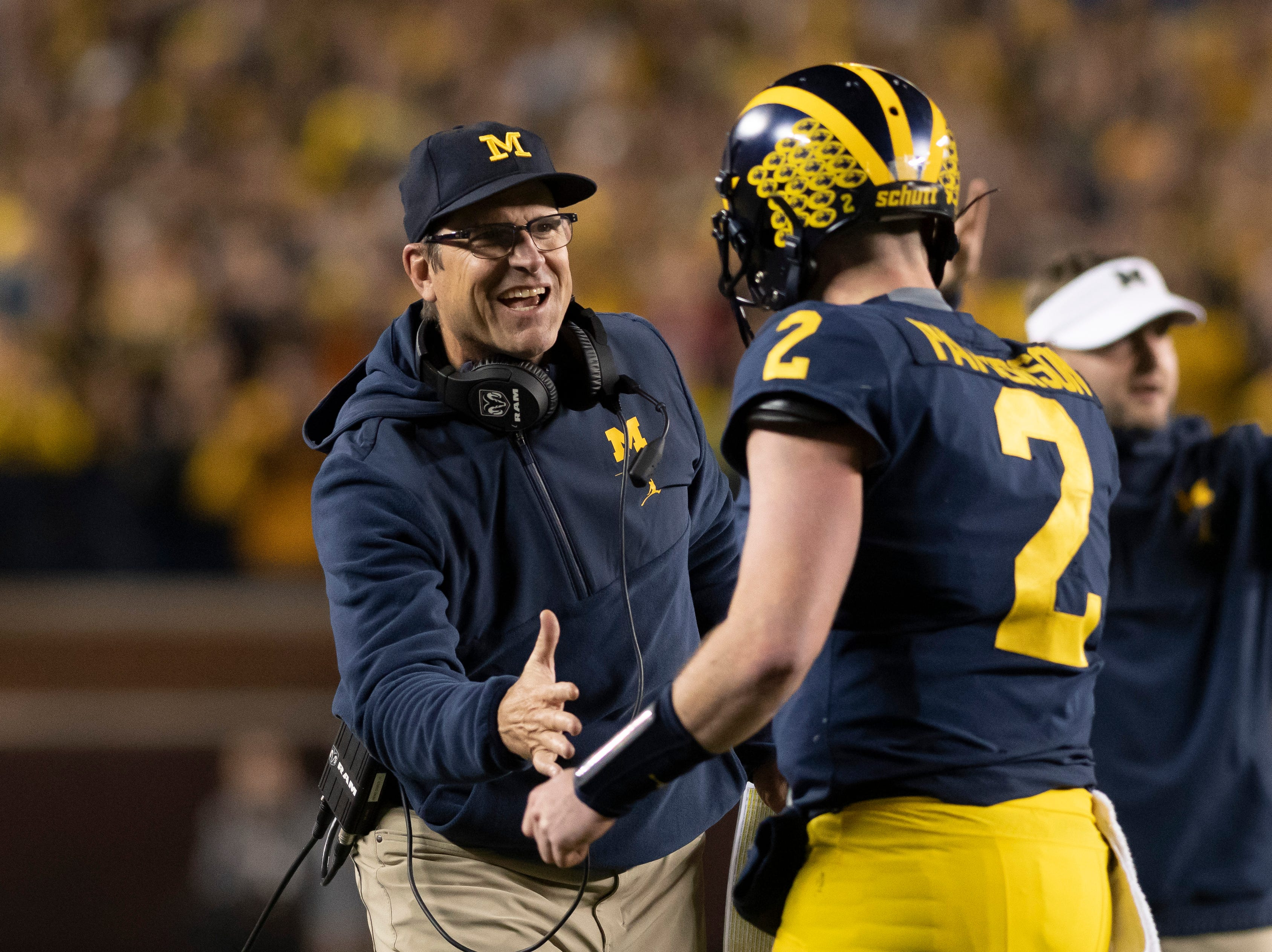 Michigan head coach Jim Harbaugh shakes quarterback Shea Patterson's hand after a touchdown in the second quarter.