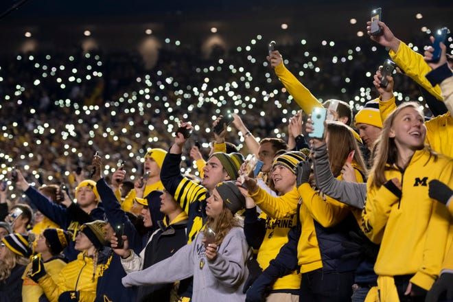 Fans use their cell phones to illuminate the stadium while singing during a timeout in the fourth quarter.