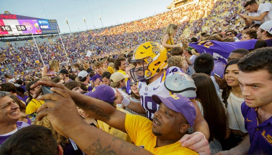 LSU's Foster Moreau is surrounded as fans rush the field after the victory over No. 2 Georgia.