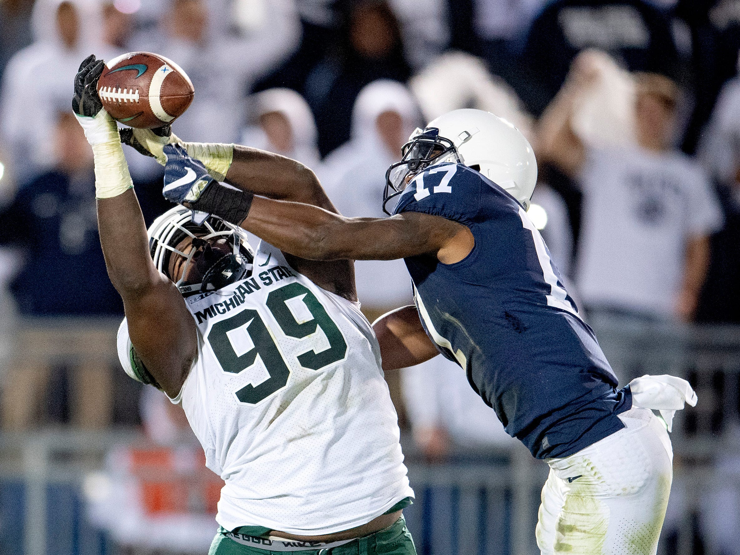 Penn State safety Garrett Taylor, right, knocks the ball away from Michigan State defensive tackle Raequan Williams at Beaver Stadium in University Park, Pa., on Saturday, Oct. 13, 2018. The visiting Spartans won, 21-17. (Abby Drey/Centre Daily Times/TNS)