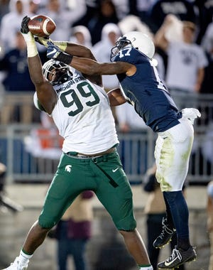 Penn State safety Garrett Taylor, right, knocks the ball away from Michigan State defensive tackle Raequan Williams.