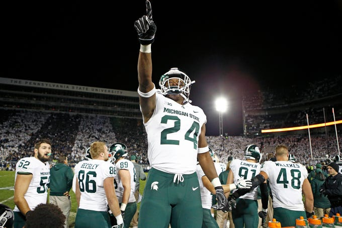 Michigan State's Elijah Collins stands on the bench and celebrates after his team scored against Penn State with 19 seconds left in a 21-17 victory Saturday, Oct. 13, 2018, in State College, Pa.