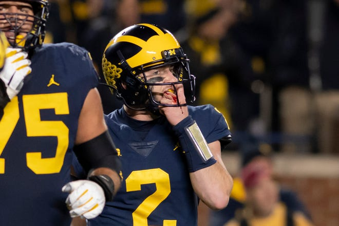 Michigan quarterback Shea Patterson has blood on his left hand after running for a touchdown in the third quarter Saturday.