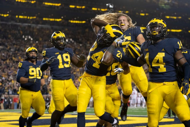 Michigan defensive back Lavert Hill (24) and his teammates celebrate after Hill scored a touchdown after an interception in the fourth quarter.