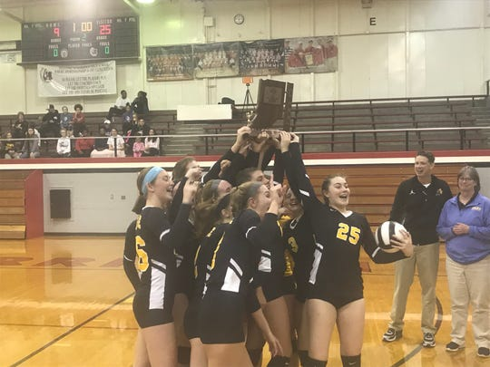 Castle's volleyball players proudly hoist the Class 4A sectional championship trophy