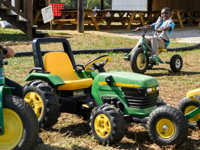Gerarod Winters, a first grade student from Glenwood Leadership Academy, races other classmates on toy John Deere tractors and tricycles during a field trip to Cate's Farm Corn Maze and Pumpkin Patch in Henderson, Ky., Friday, Oct. 12, 2018. The farm offers field trips for school  groups during the week and is open to the general public on Fridays from 4-9 p.m., Saturdays from 10 a.m.- 9 p.m. and Sundays from 1-7 p.m. until October 31.