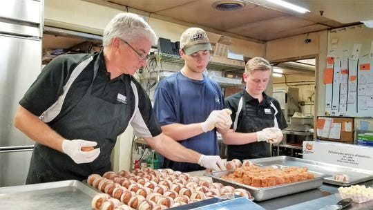 "Tony Marx, left, makes pork grenades with William Rodenberg, center, and Tanner Rexing, who have worked at Marx for eight and four years, respectively. Now that they are in college, they come back to help during fall break and holidays. ""They are good bosses and we make great food,"" said Rodenberg. ""It's a good place to be."""
