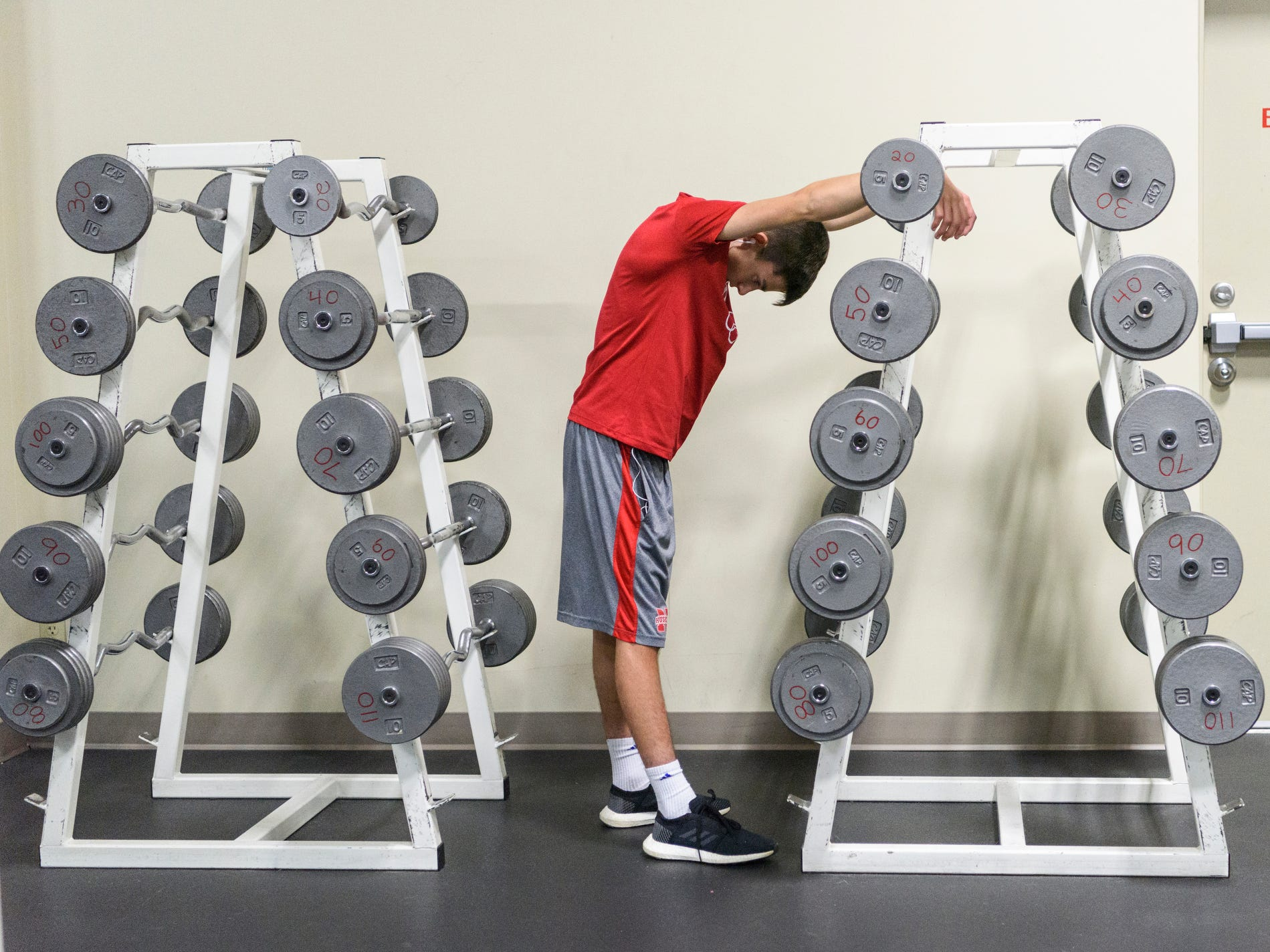 Sam Archuleta takes a moment to catch his breath and stretch during a workout at Elite Fitness in Evansville, Ind., Thursday evening, Oct. 11, 2018.