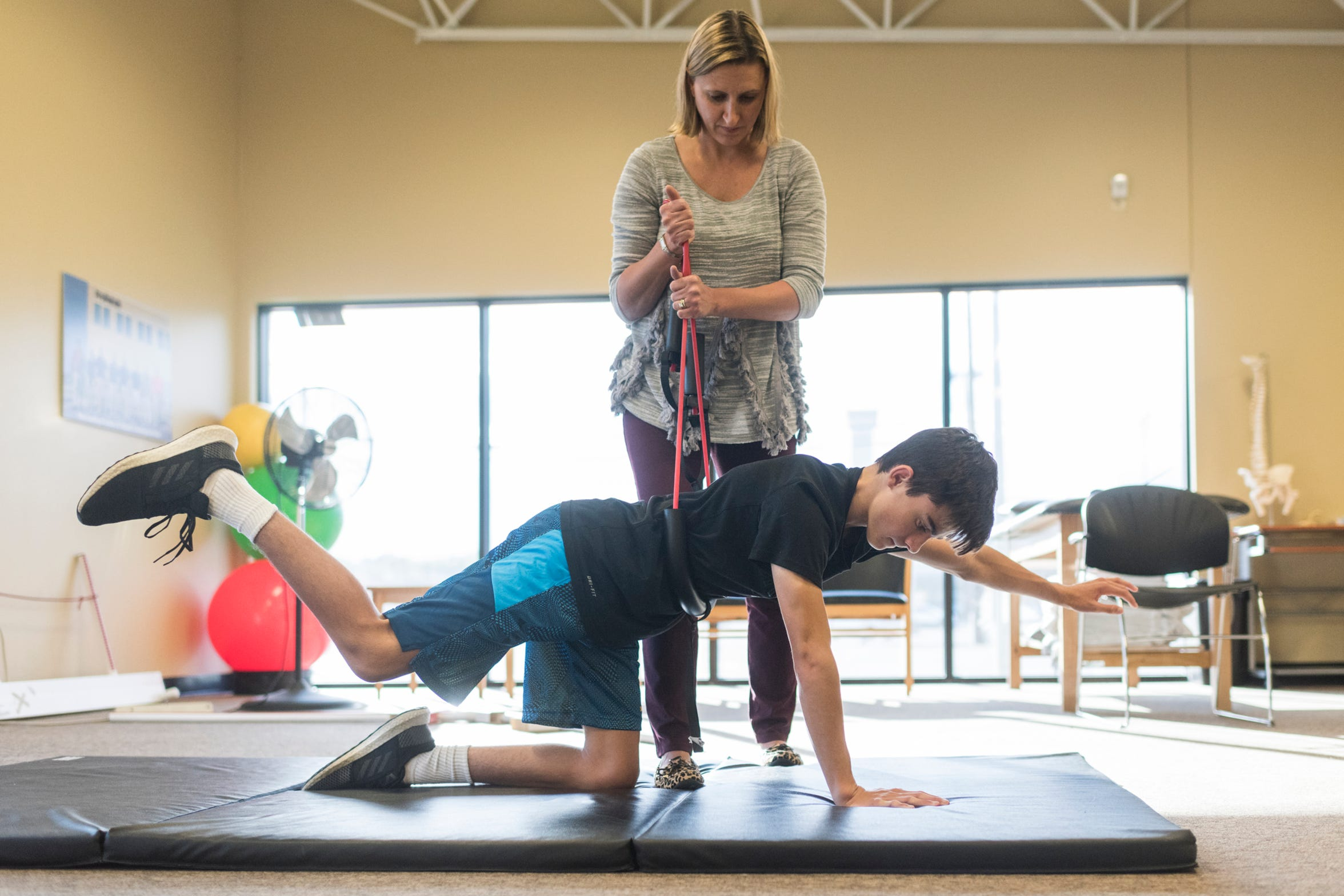 Physical Therapist Natalie Hussmann, top, helps Sam Archuleta, front, during an appointment at Pro Rehab in Evansville, Ind., Wednesday, Oct. 10, 2018. They meet once a week to build his strength to combat the effects of Friedreich's ataxia (FA).