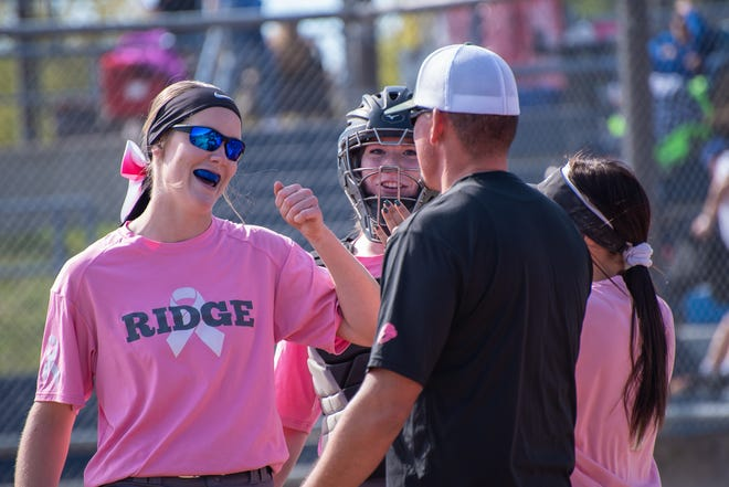 Fossil Ridge High School pitcher Kate Delaney (16) gets a fist bump from head coah Walker Damge during a regional softball game against Rampart on Saturday, October 13, 2018, at Rolland Moore Park.