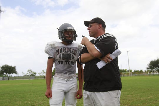 Mariner High School football coach Chris Siner talks with quarterback Andrew Torres during practice in 2011.