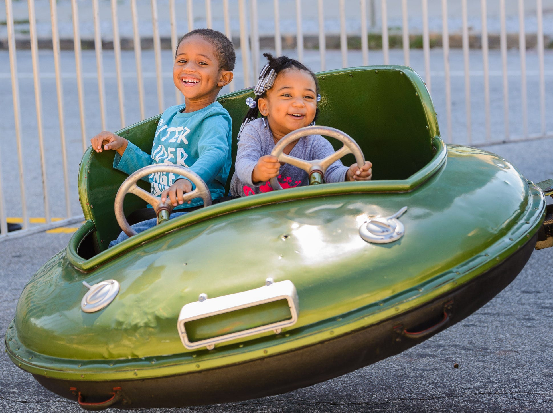 4 year old Cavin Fuller (left) and his 3 year old sister Cy have fun riding in the Spaceships at Fall for Greenville in Downtown Greenville on Saturday, October 12, 2018.