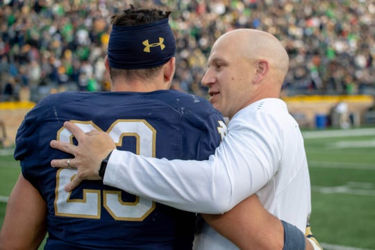 Fighting Irish Defensive Coordinator Clark Lea celebrates with linebacker Drue Tranquill (23) after Notre Dame defeated the Pittsburgh Panthers at Notre Dame Stadium.