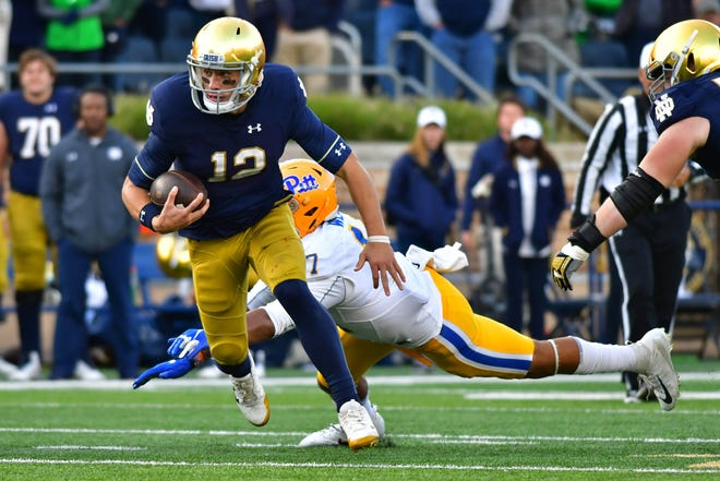 Notre Dame Fighting Irish quarterback Ian Book (12) escapes pressure by Pittsburgh Panthers defensive end Rashad Weaver (17) in the fourth quarter at Notre Dame Stadium.