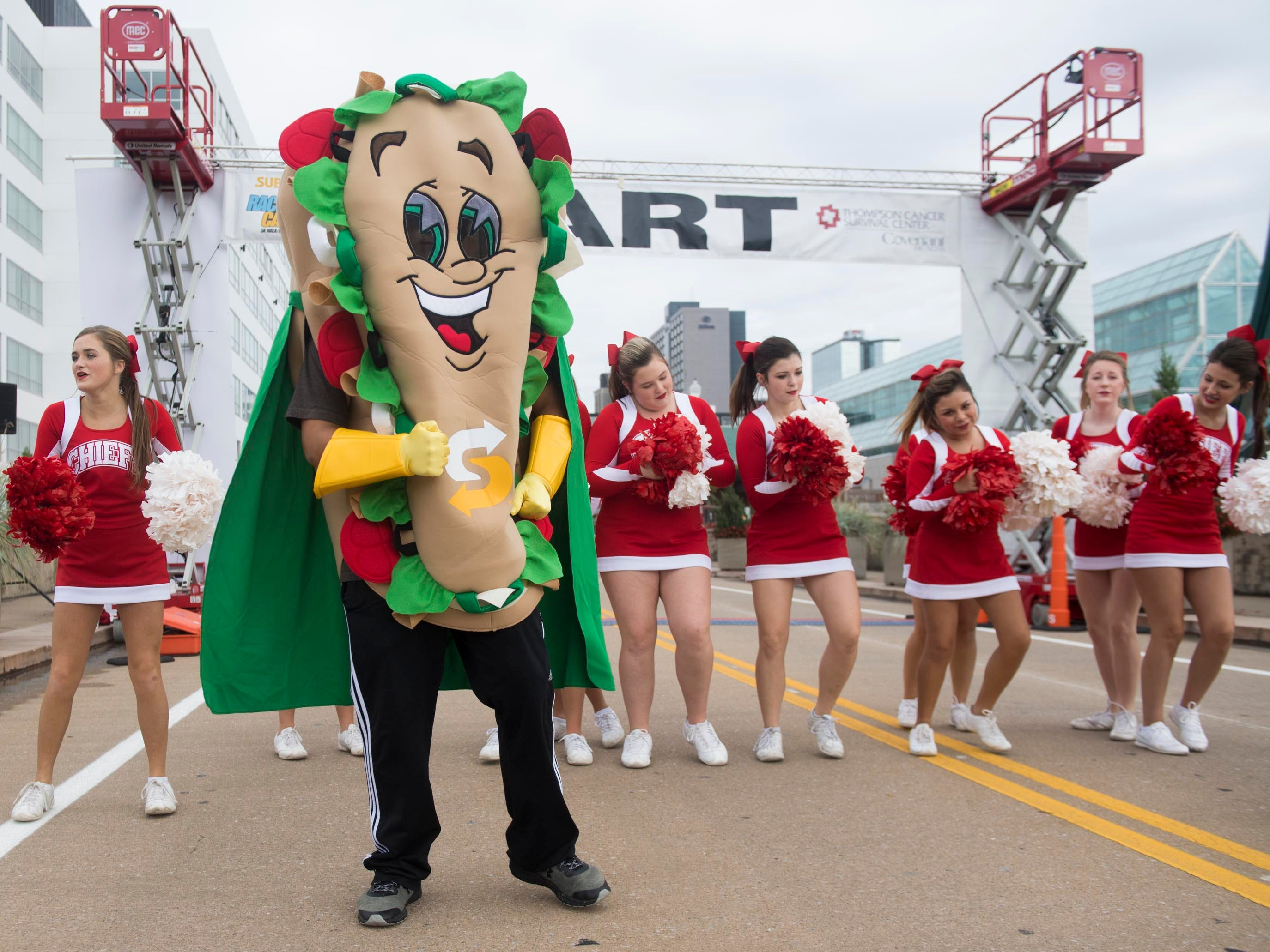 A Subway mascot and cheerleaders from Sequoyah High School in Madisonville cheer on the runners as they line up at the starting line for Covenant Health's Subway Race Against Cancer at World's Fair Park on Sunday, October 14, 2018.