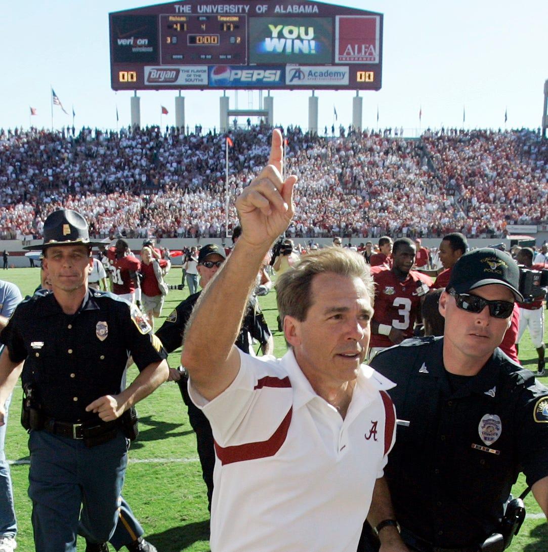Alabama coach Nick Saban runs off the field after...