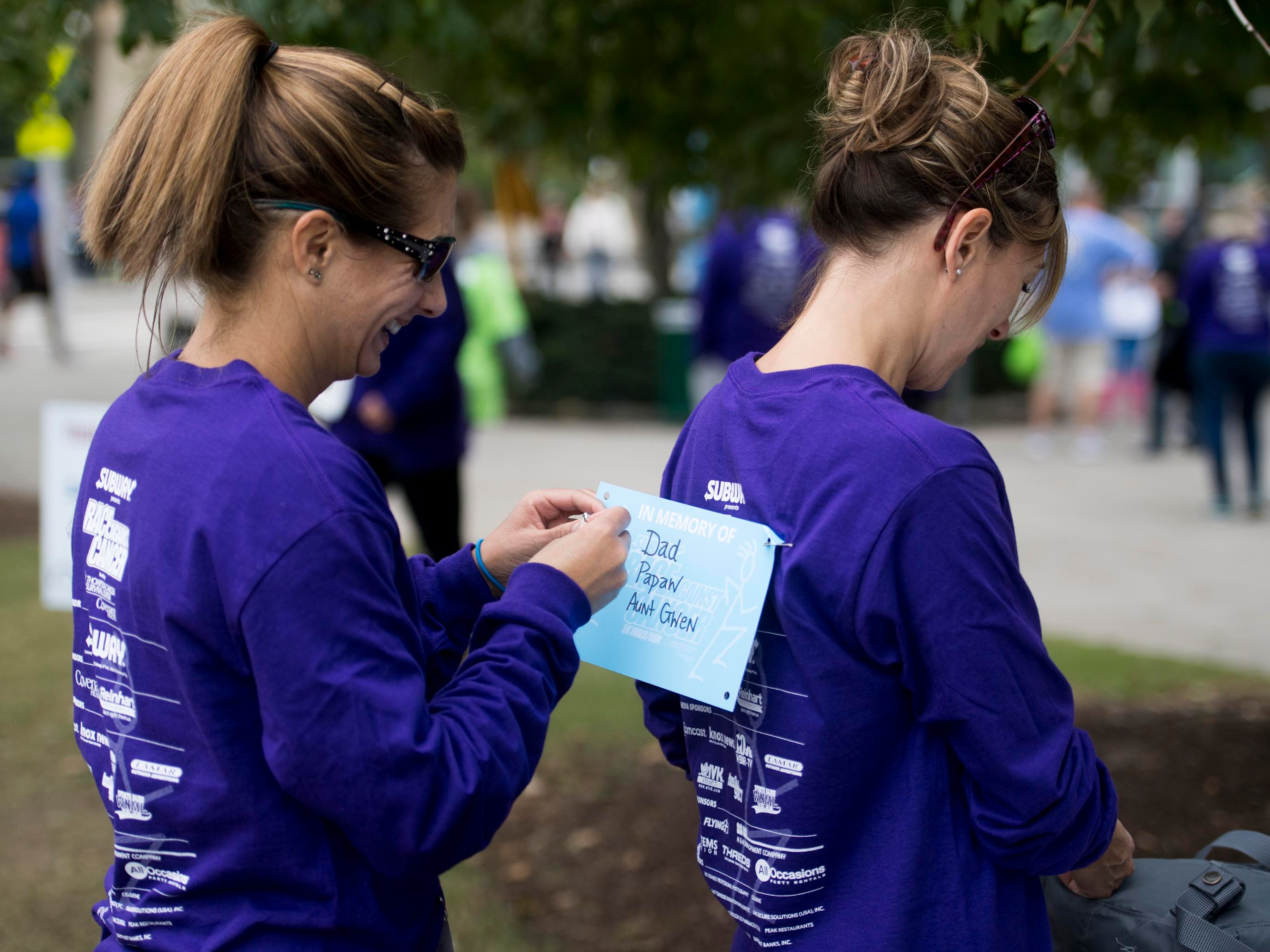Erika Nickless and Kristin Kerr prepare to run in Covenant Health's Subway Race Against Cancer at World's Fair Park on Sunday, October 14, 2018. On Nickless back is a sign recognizing her father Daryl Kerr, grandfather William Kerr, and and Gwen Lynn.