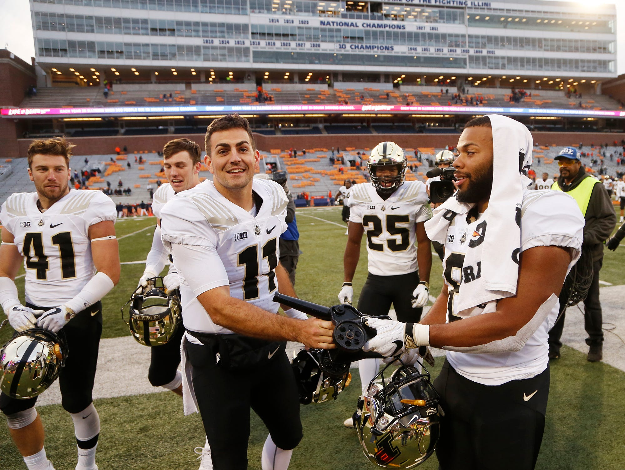 Purdue quarterback David Blough and running back Markell Jones grab The Cannon traveling trophy as they celebrate with their teammates after defeating Illinois 46-7 Saturday, October 13, 2018, in Champaign, Illinois.