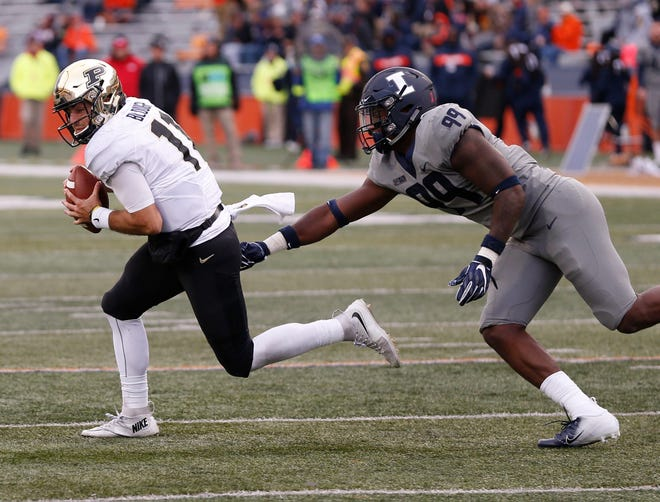 Purdue quarterback David Blough gets chased by Owen Carney of Illinois in the second half Saturday, October 13, 2018, in Champaign, Illinois. Purdue thumped Illinois 46-7.