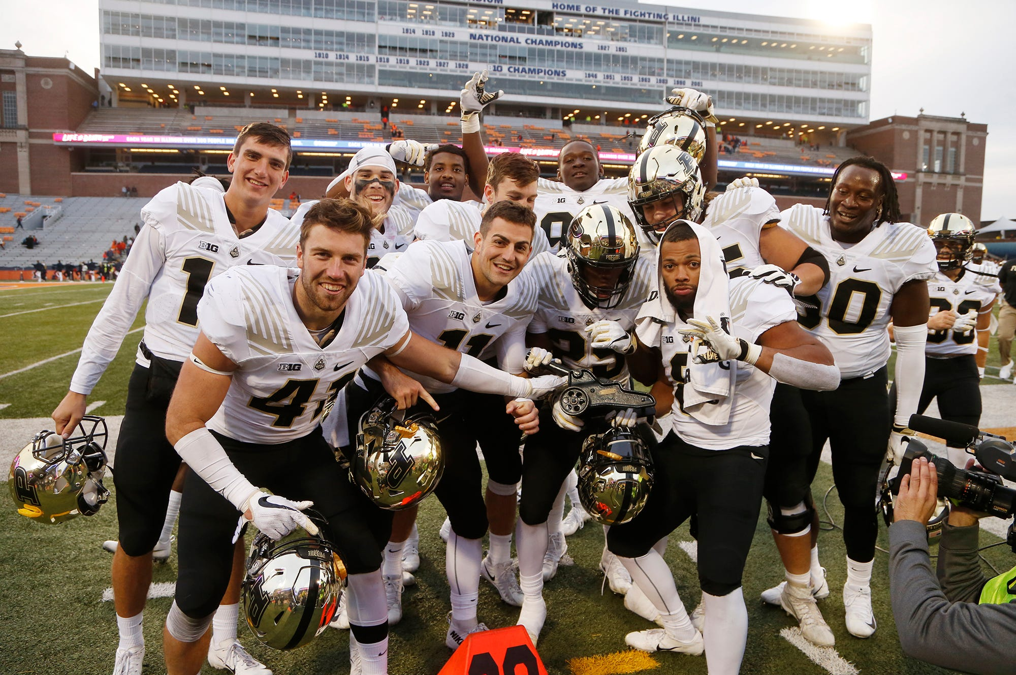 Purdue players quickly gather with The Cannon traveling trophy for photos defeating Illinois 46-7 Saturday, October 13, 2018, in Champaign, Illinois.
