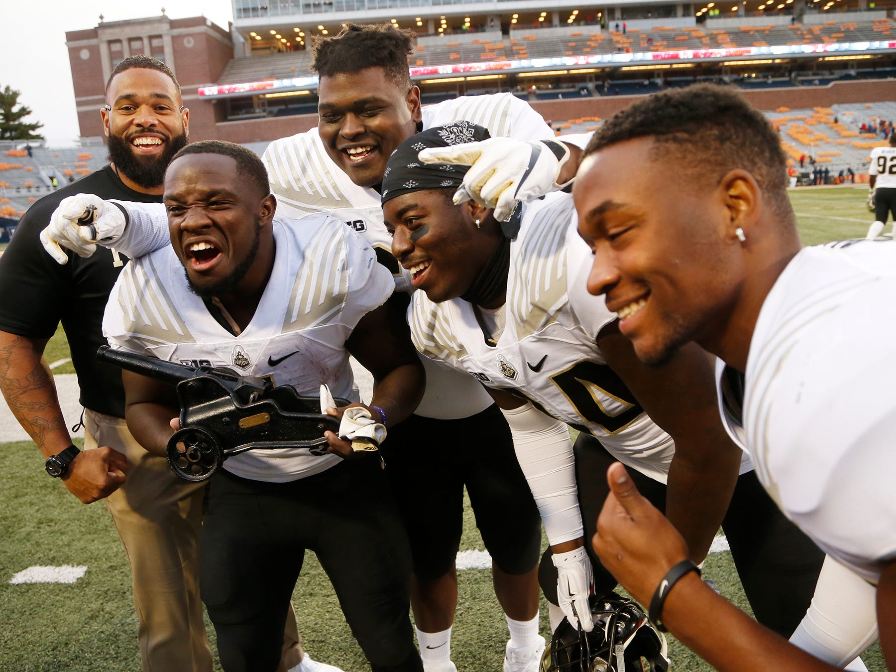 D. J. Knox, left, and his teammates celebrate with The Cannon traveling trophy after the Boilermakers pounded Illinois 46-7 Saturday, October 13, 2018, in Champaign, Illinois.